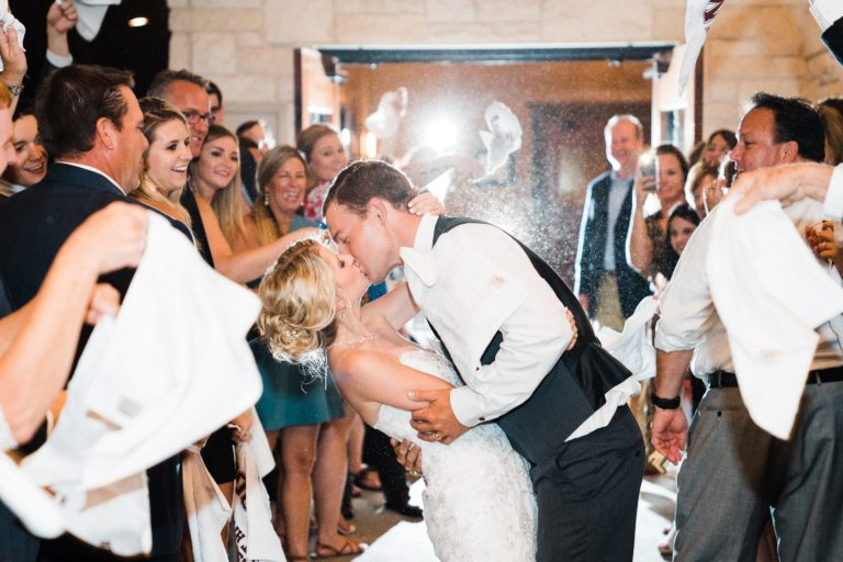 Bride and Groom kiss while people cheer