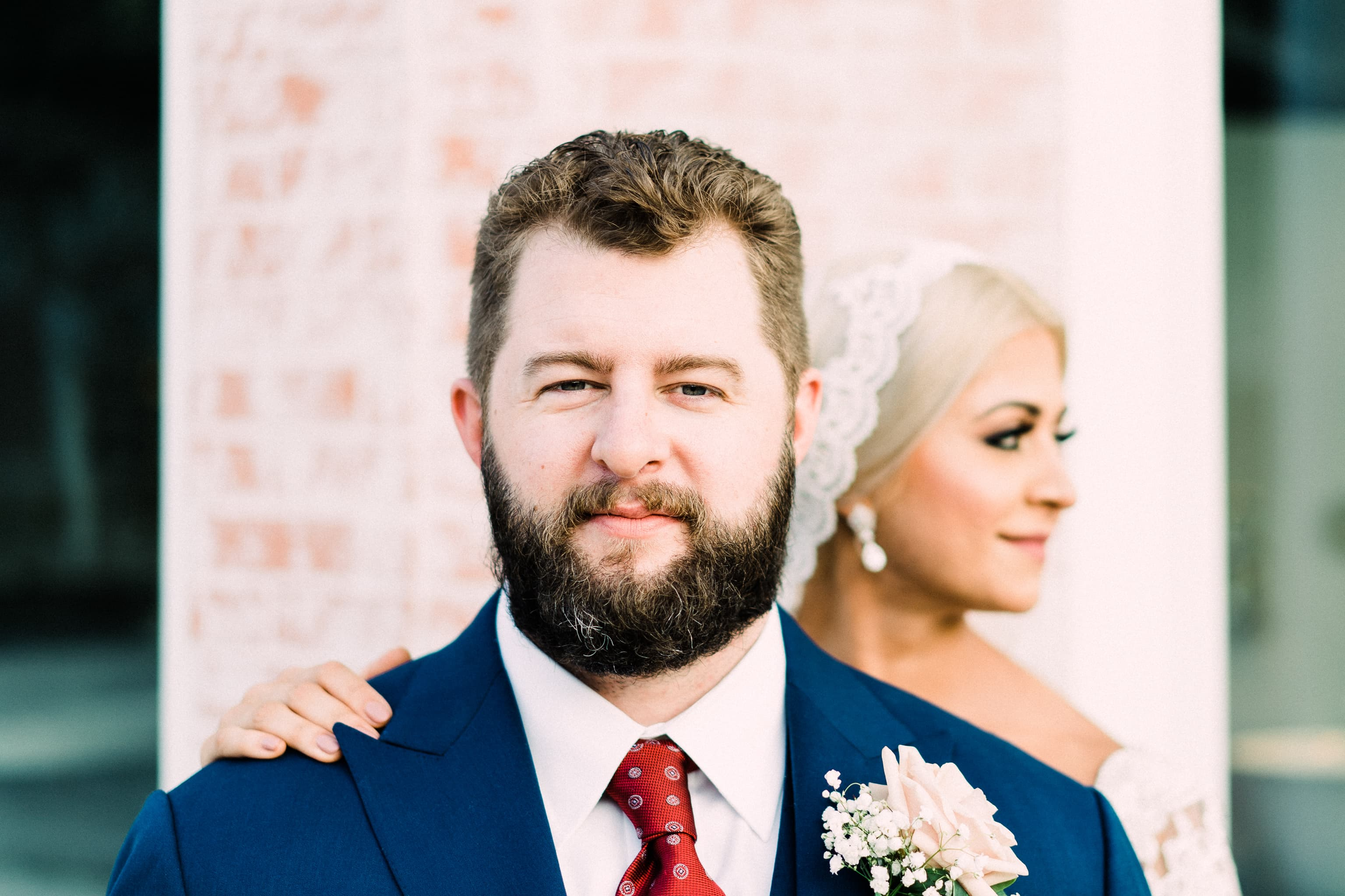 Groom stares into the camera while bride looks away.