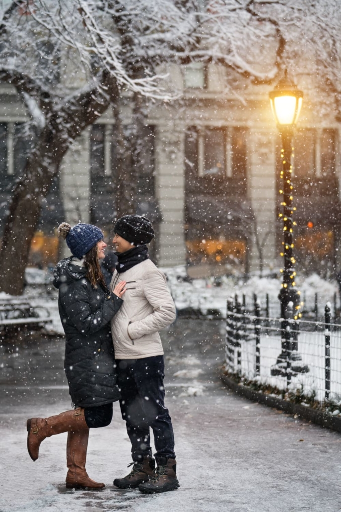 Engagement portrait in the snow by a bright lamp.
