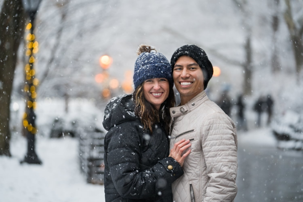 Couple smiles while embracing in a snowy park.