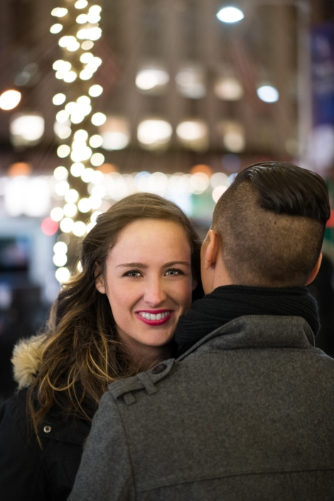 Woman smiles during embrace at Christmas.