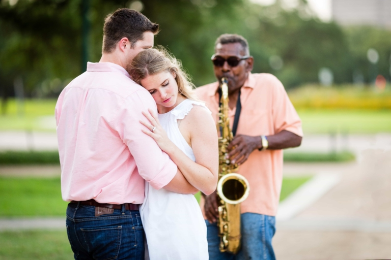 Couple dances outdoors while a man plays saxophone.