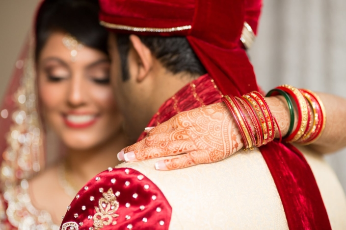 Indian bride smiles while putting her arm around her husband.