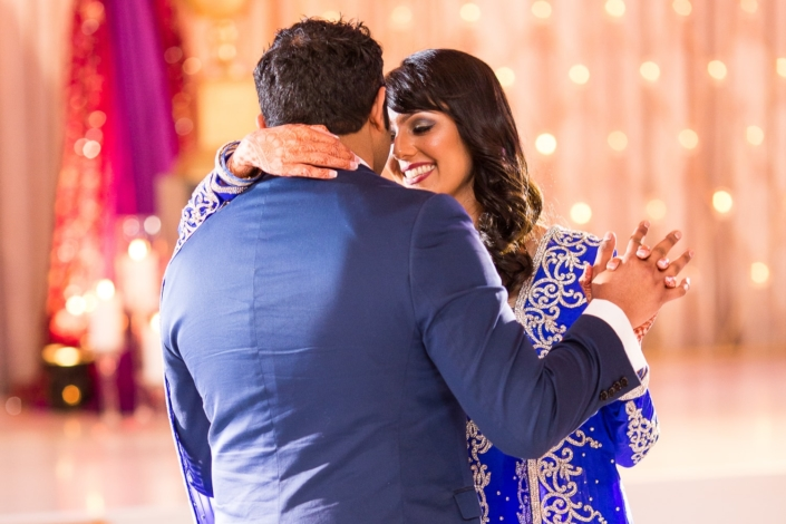 Indian couple embrace during their first wedding dance.