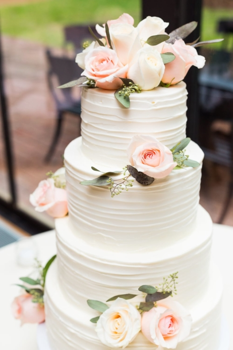 White and pink wedding cake with roses.