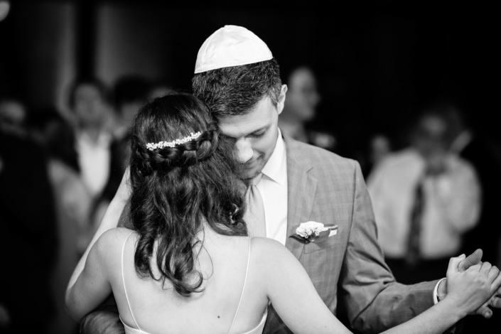 Jewish couple embraces during their first wedding dance.