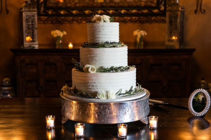 White and green wedding cake on a silver platter.