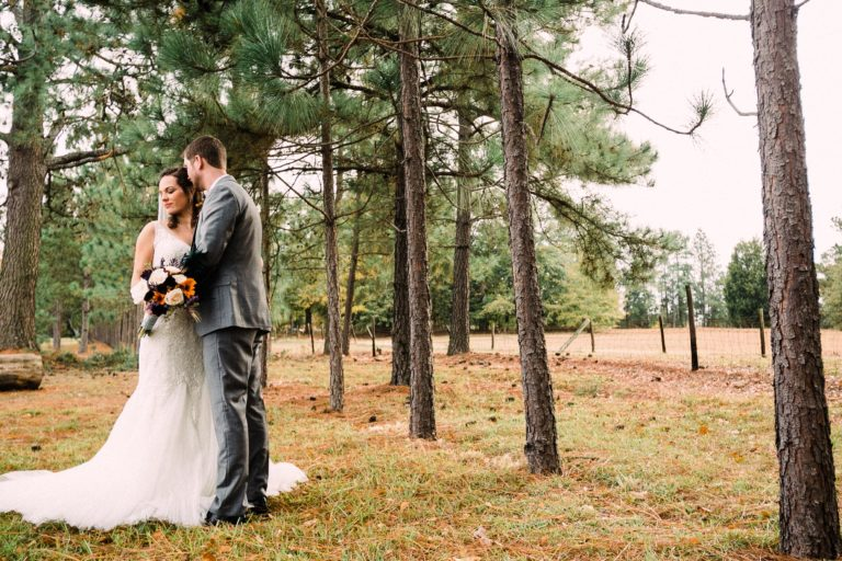 Bride and Groom embrace under pine trees