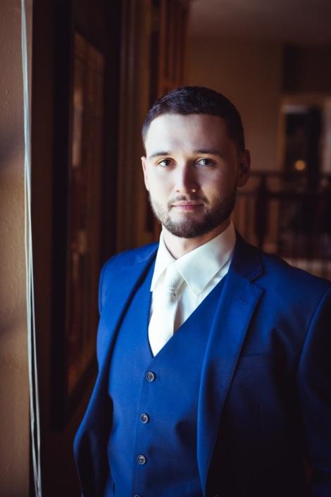Portrait of groom in blue suit.