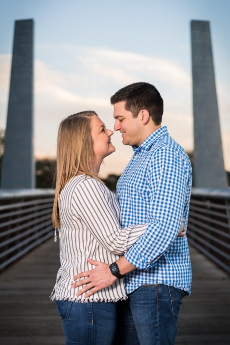 Couple embraces on bridge.