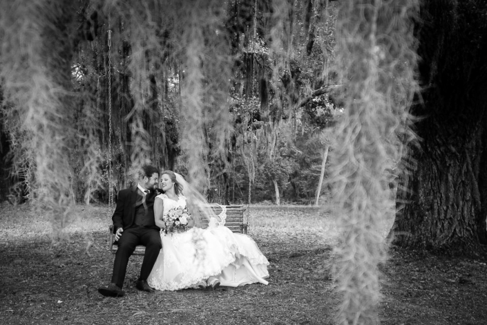 Bride and Groom smile at each other on a swing behind Spanish Moss.