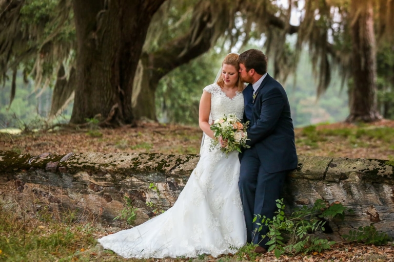 Bride and Groom embrace under a tree.