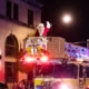 Santa waving from the top of a fire truck during a Christmas Parade.