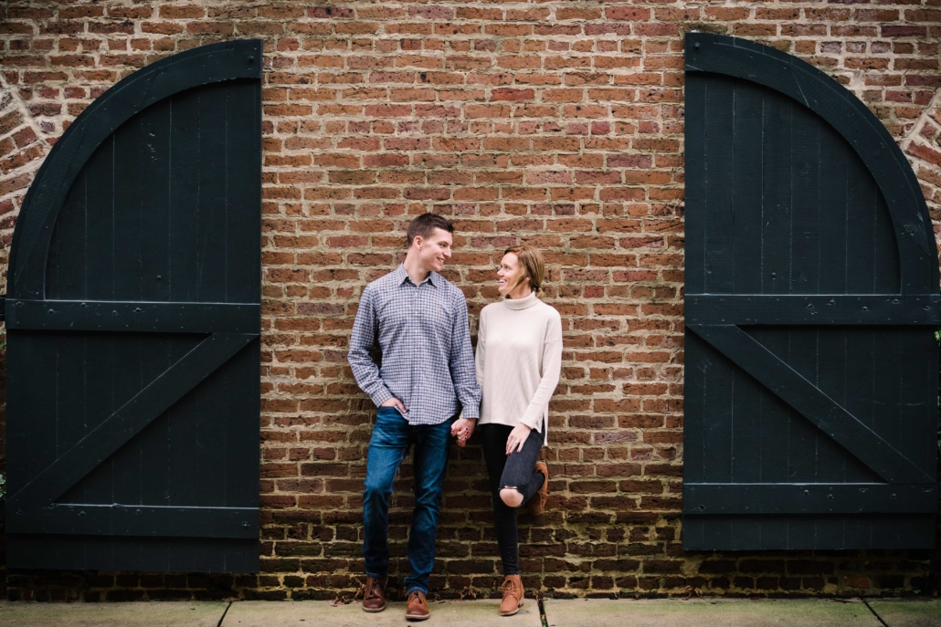 Engaged couple leans against a wall and looks at each other