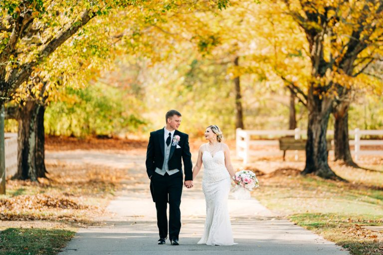 Bride and Groom walking down a road in fall