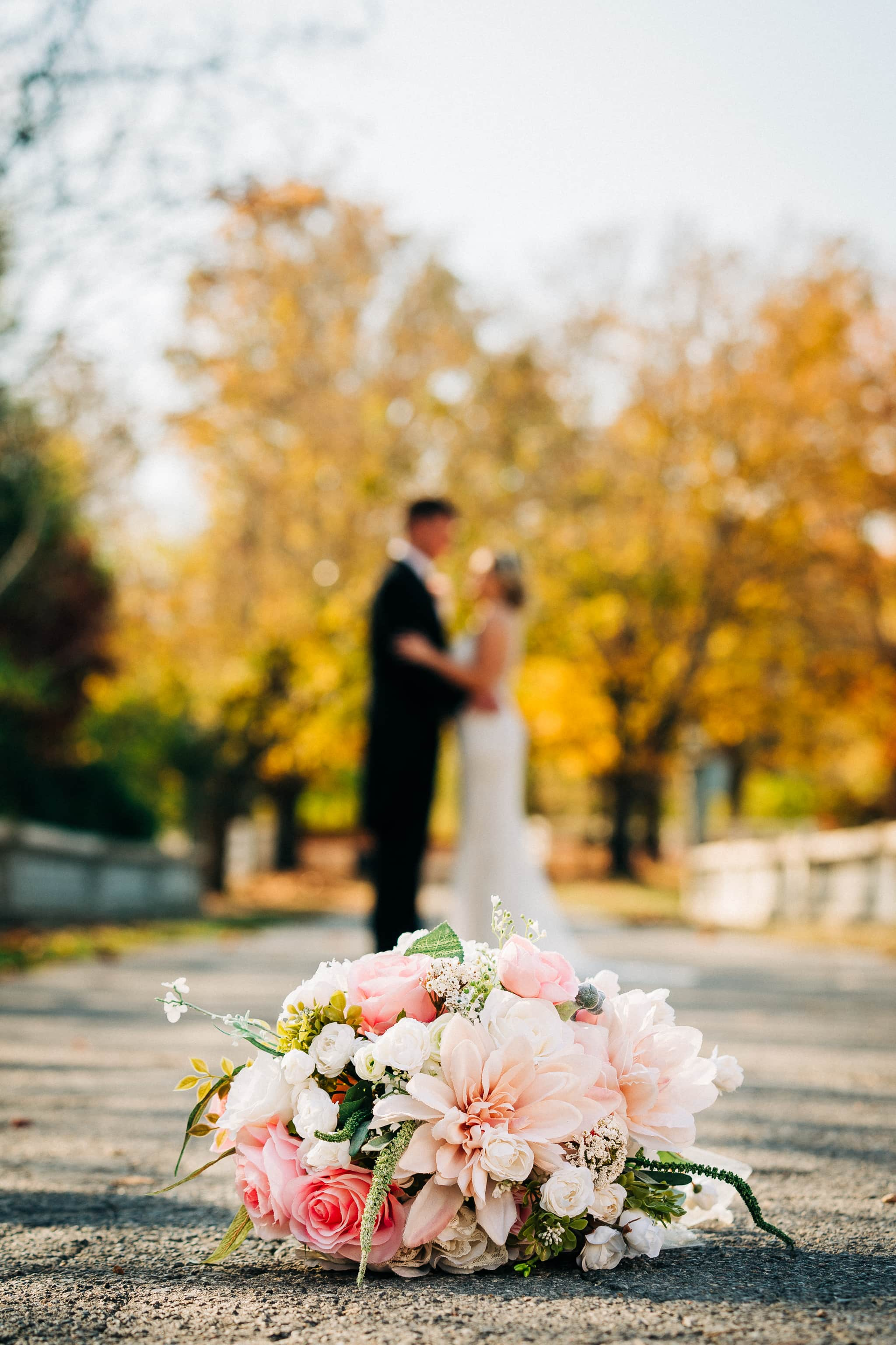 Couple embracing in the distance behind a silk bouquet.