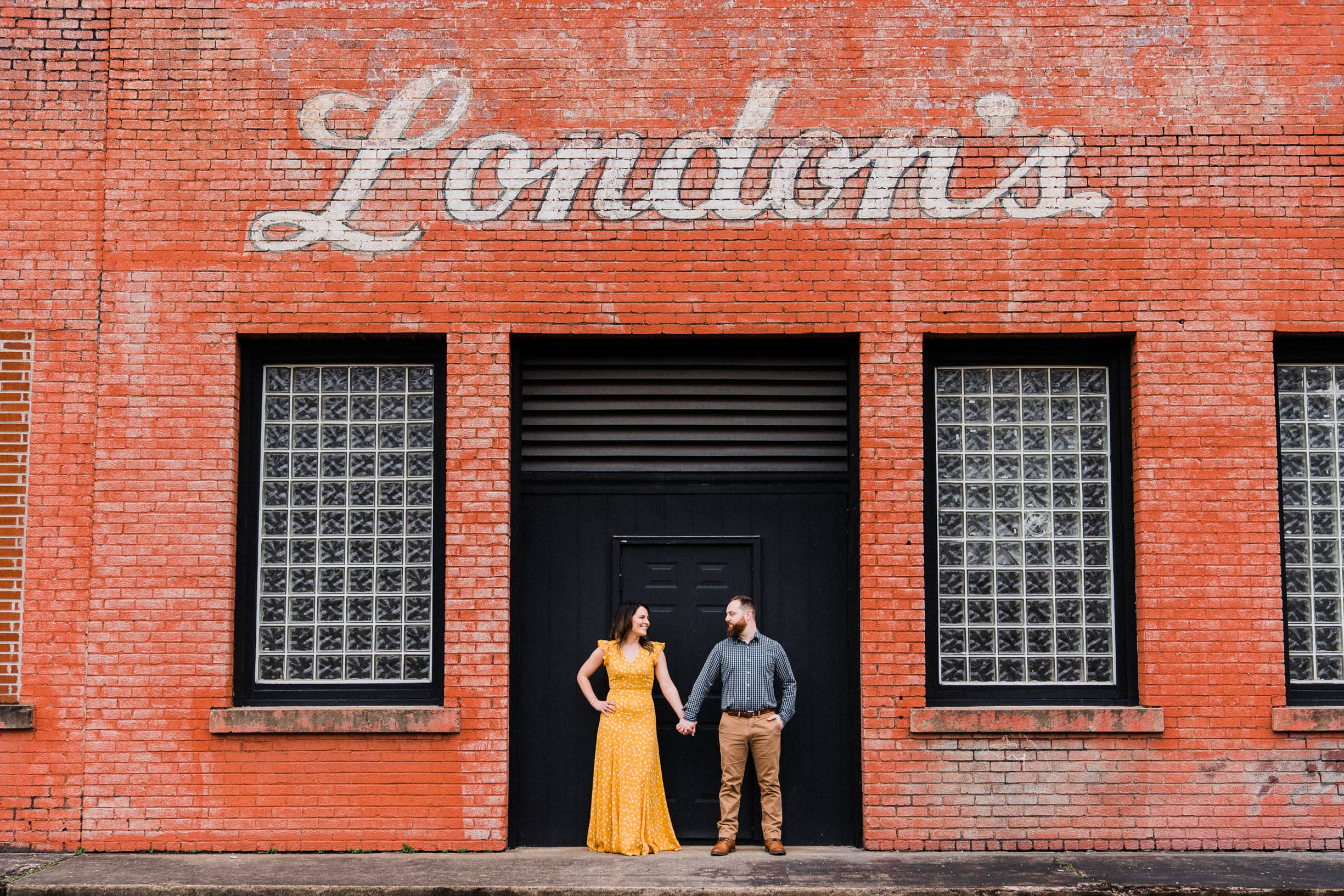 Engaged couple poses in front of London's building downtown Johnson City, Tennessee