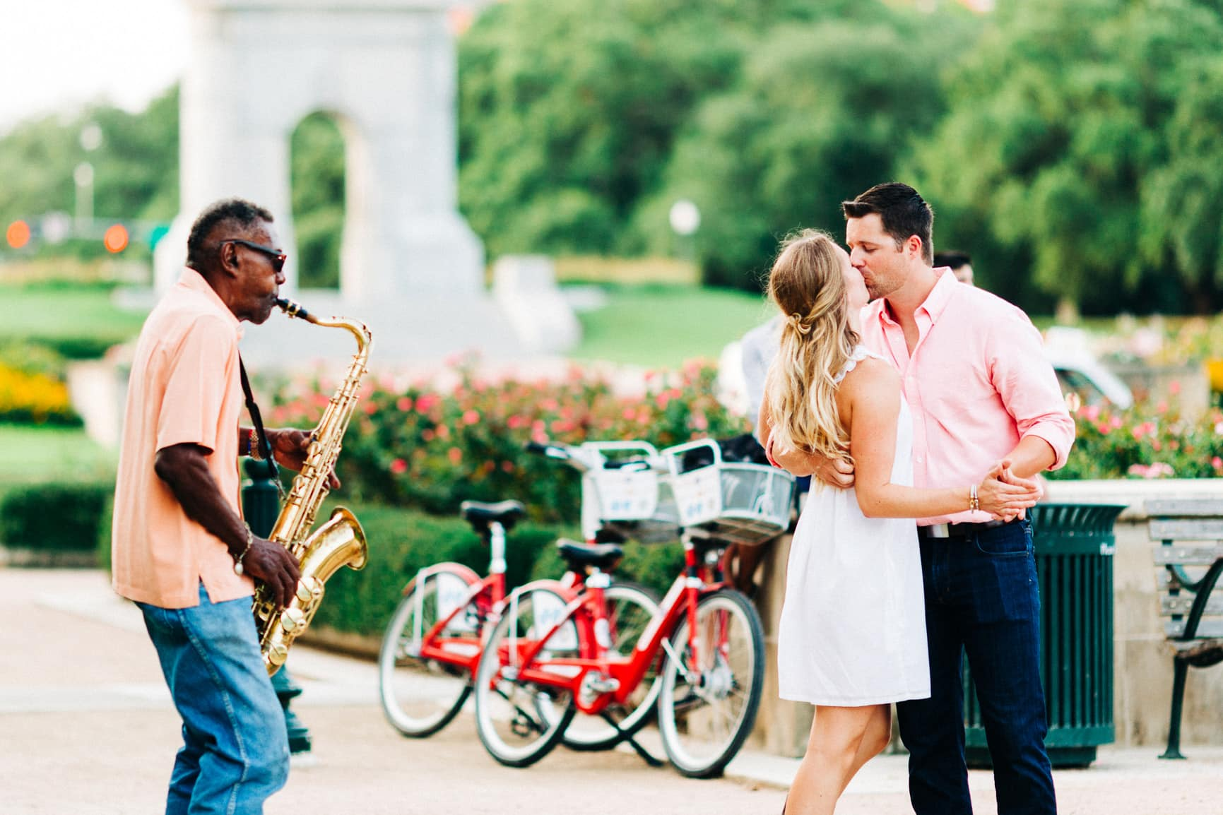 couple dance to a saxophone player in the park