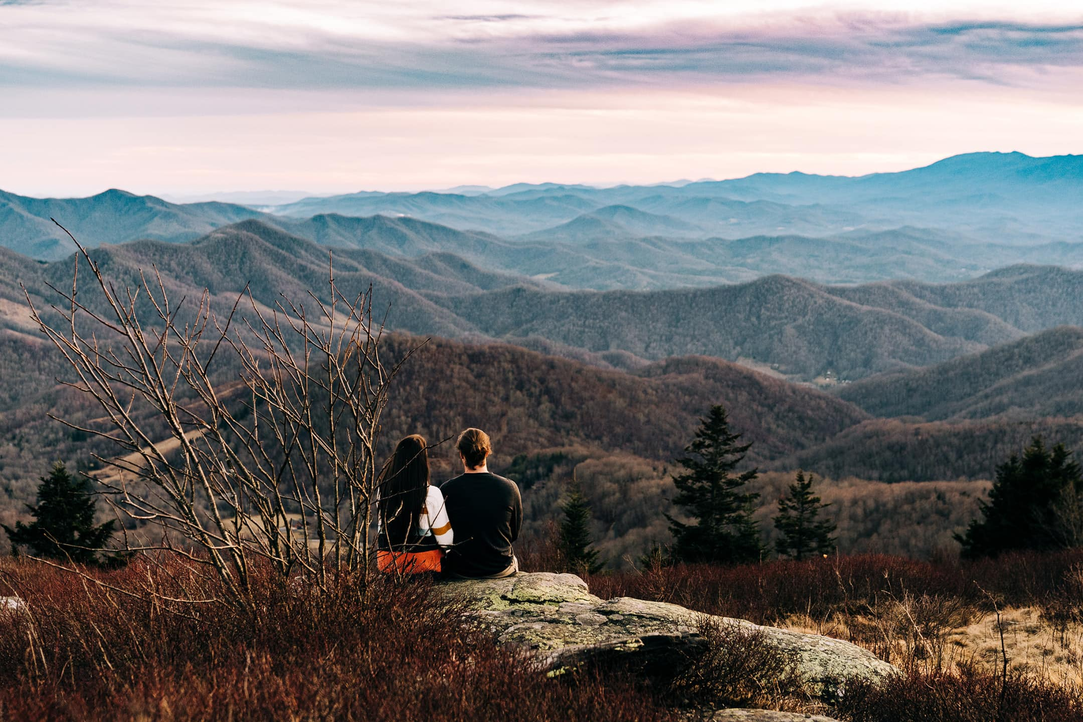Couple sits on a cliff staring over mountain tops