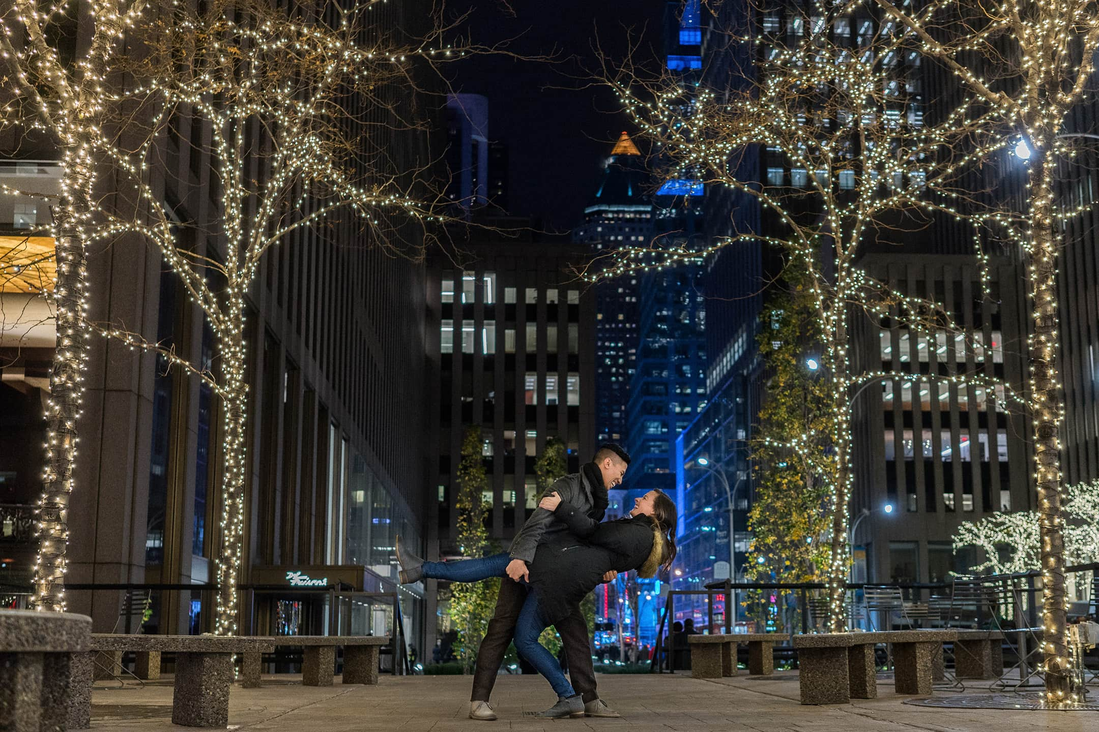 man dips a woman in front of Christmas lights in New York City