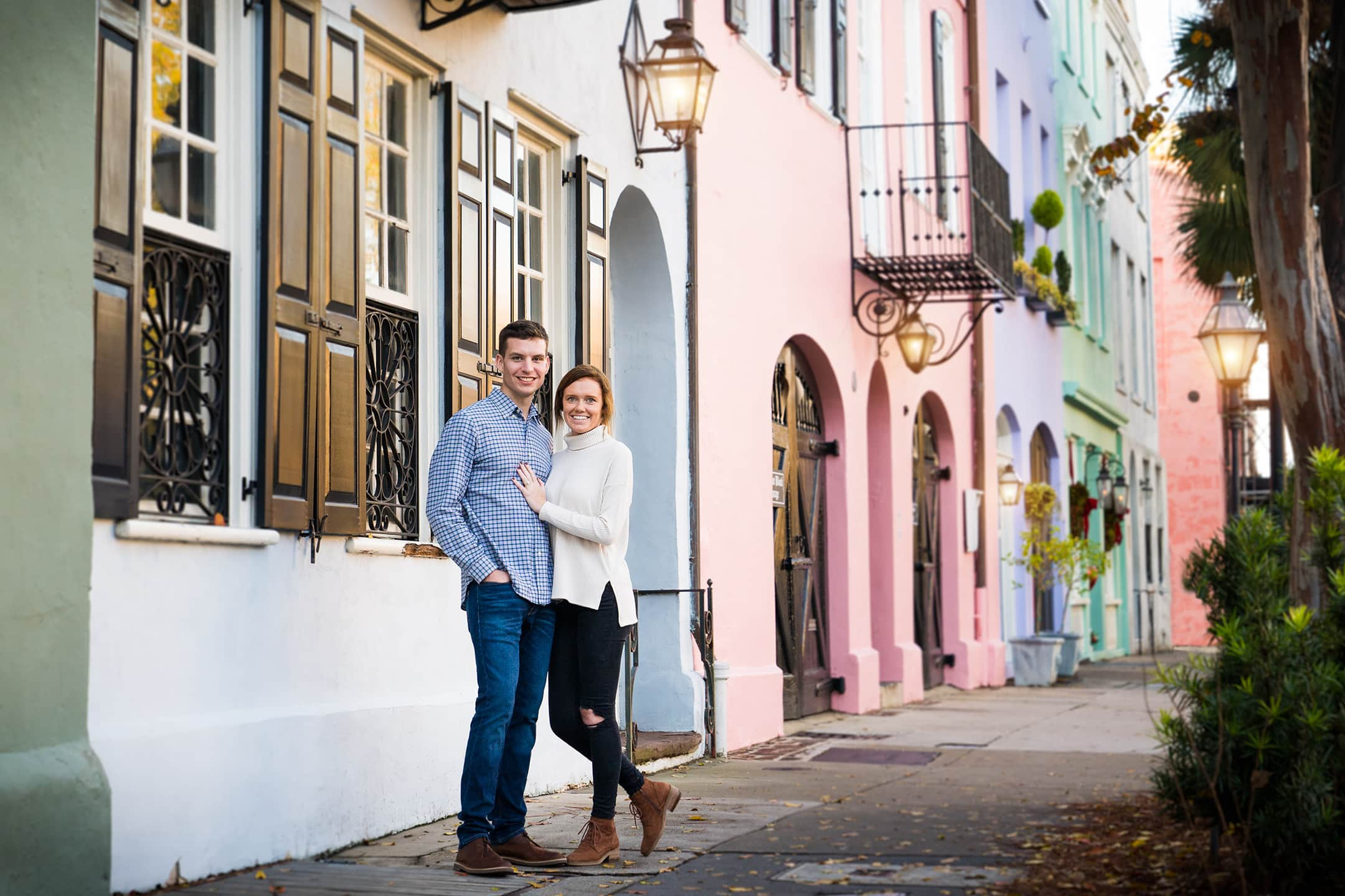 Engaged couple in front of colored houses