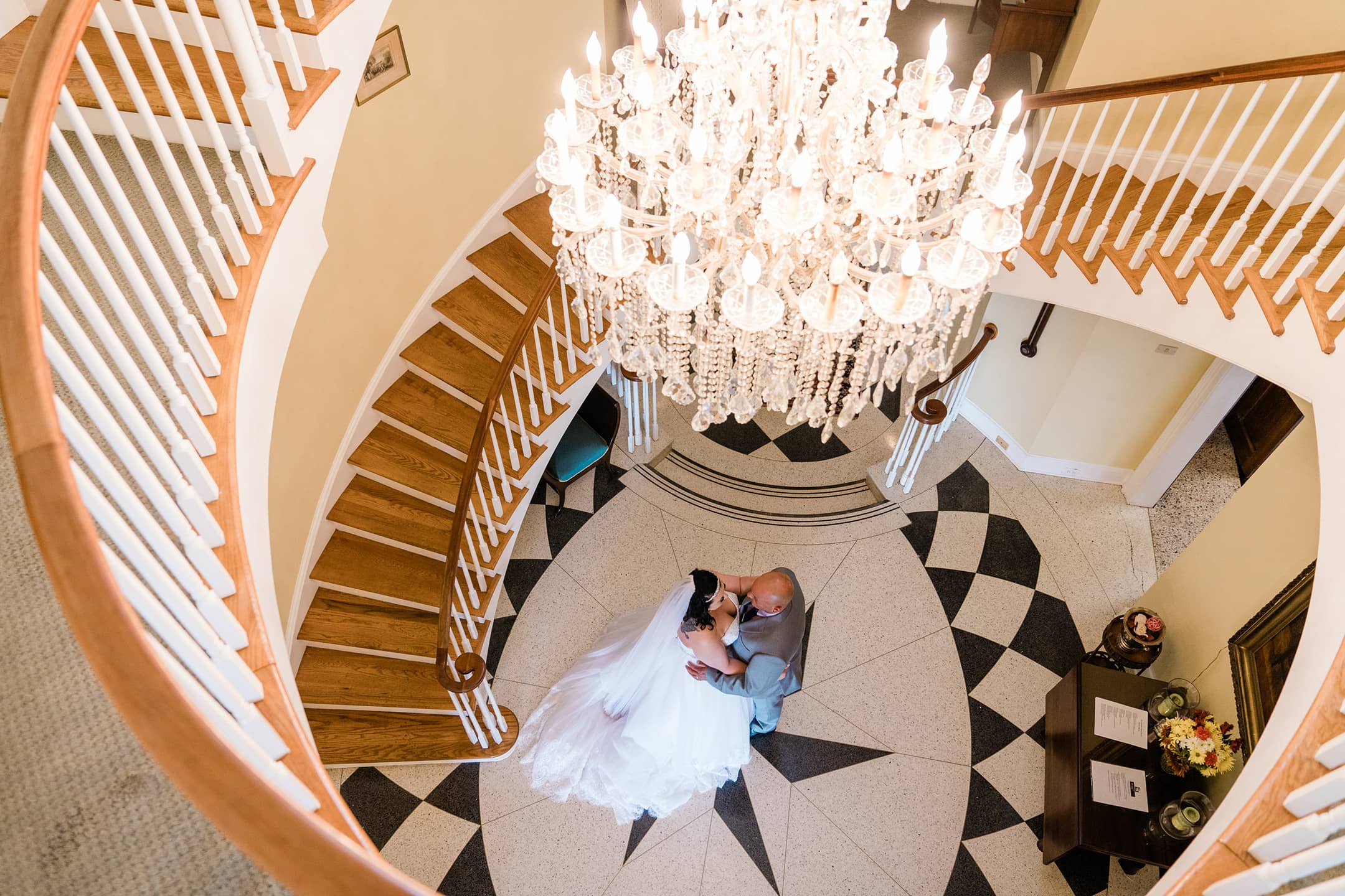 Brid and Groom embrace under an elegant chandelier and staircase