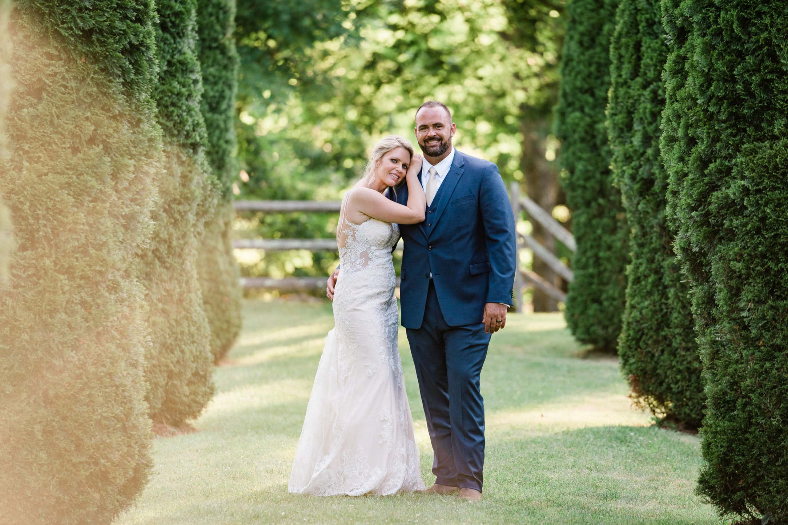 Bride and Groom embrace between sets of trees at Whispering Waters Farm