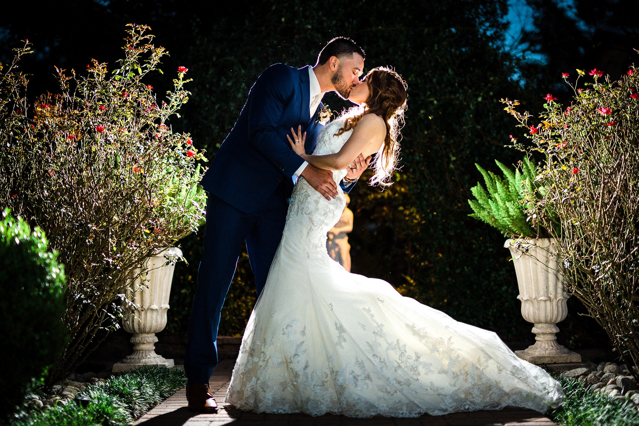 Newlyweds share a kiss at night outdoors.