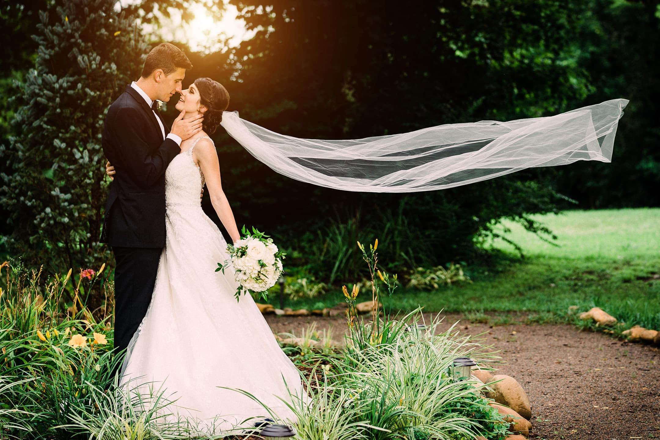 Bride and Groom embracing while her veil flies behind her