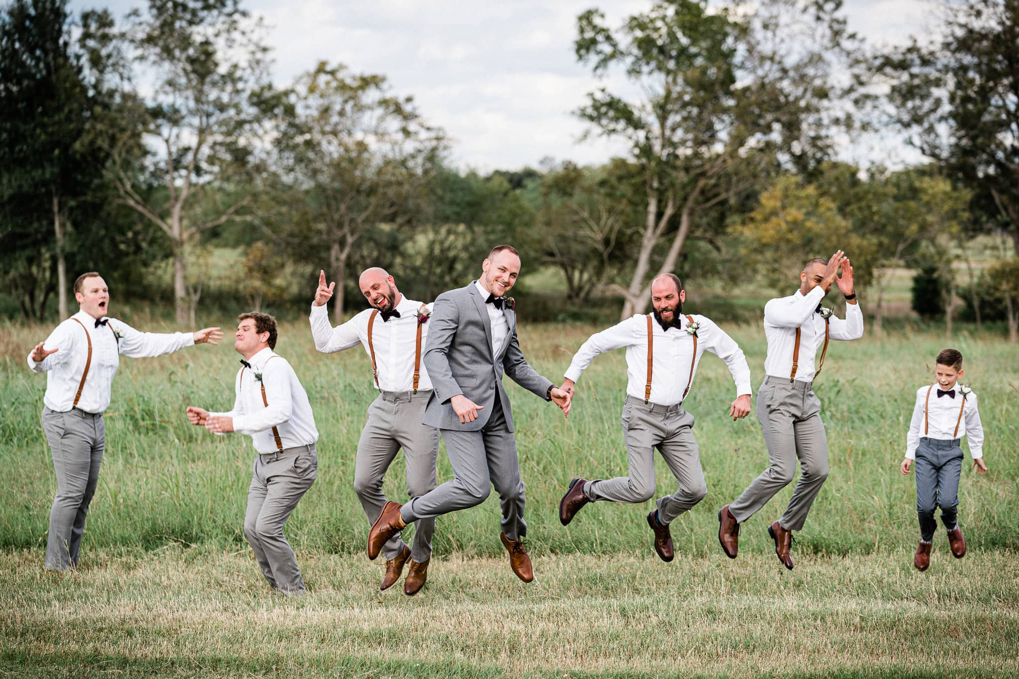 Groom and groomsmen jump together in a field