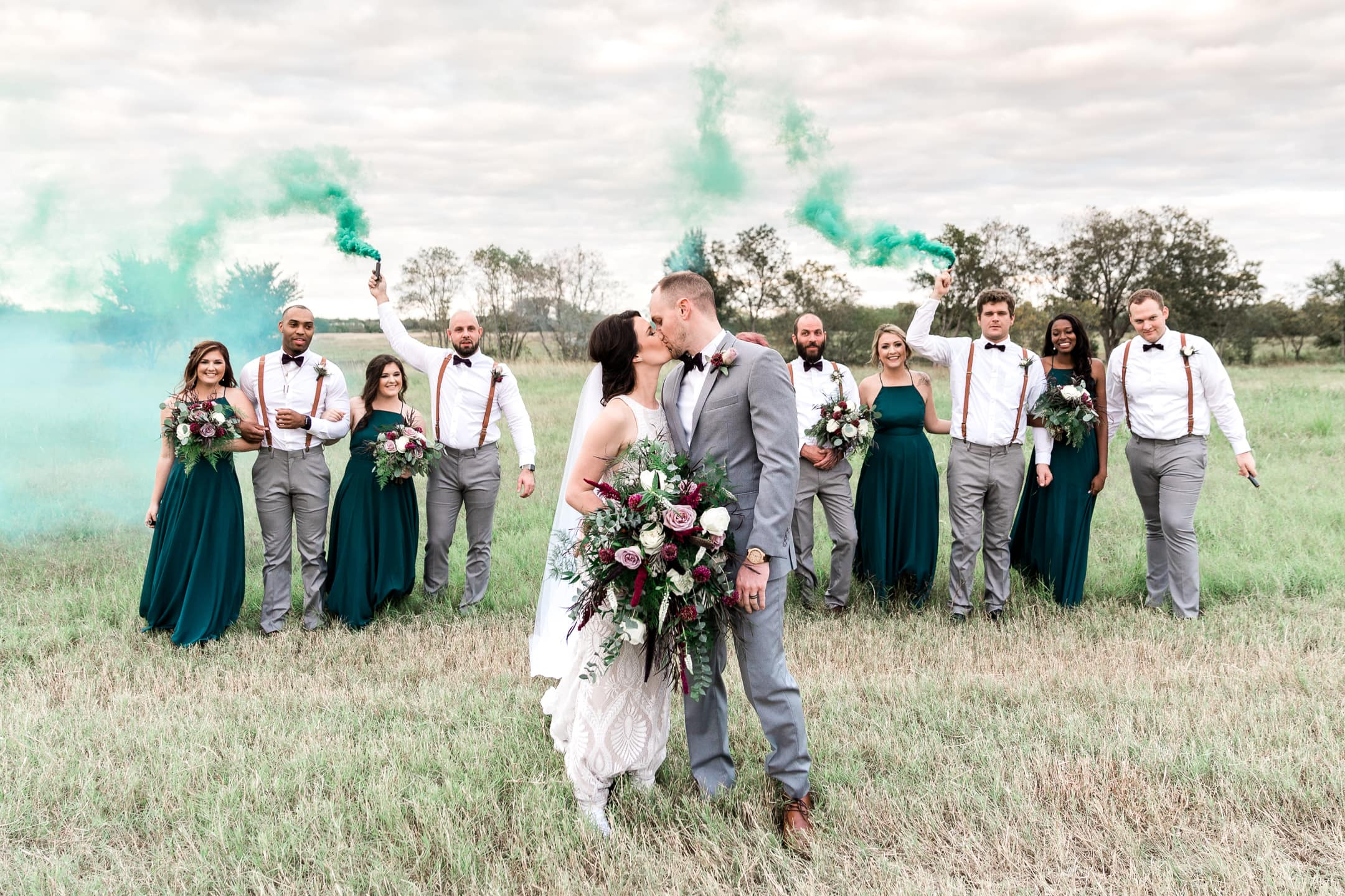 Couple kisses in a field while friends cheer and set off smoke bombs behind them