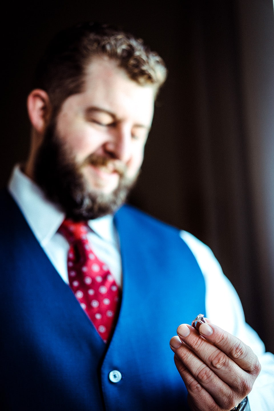 Groom smiles down at his wife's wedding ring