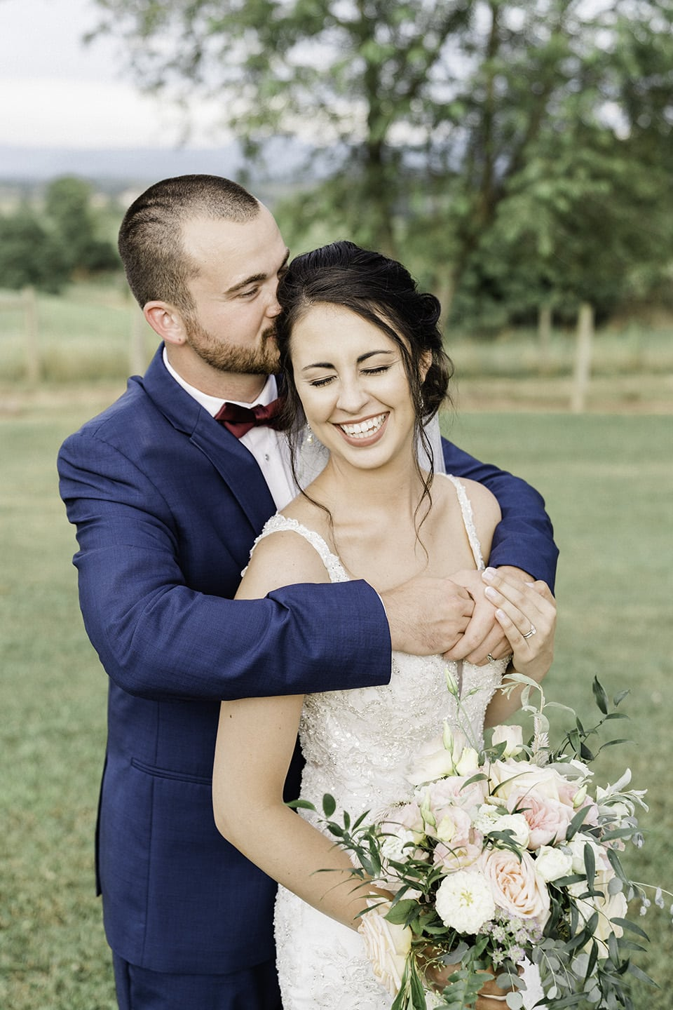 Groom hugs bride from behind while she smiles
