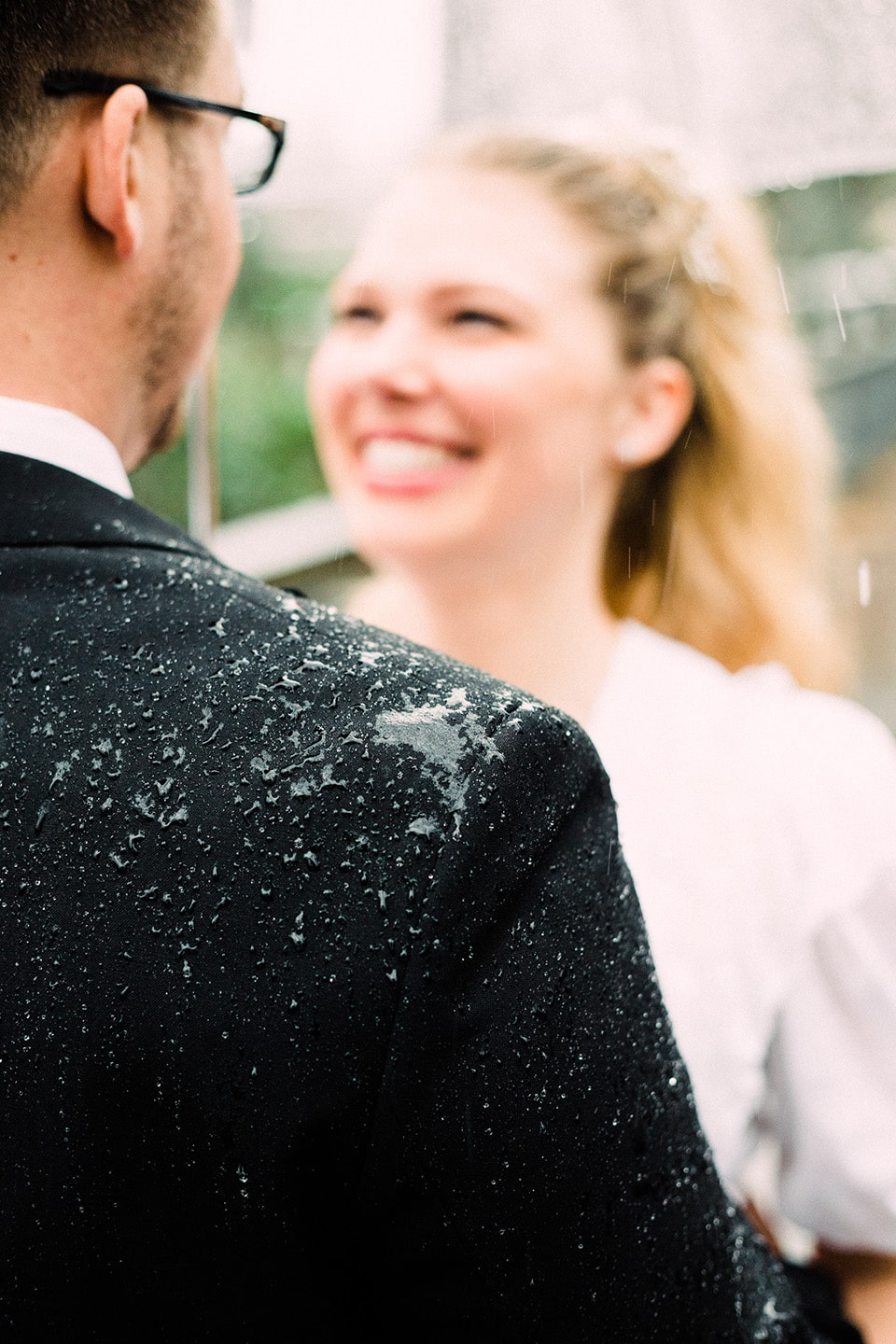 Bride smiles at groom while standing under umbrella in the rain