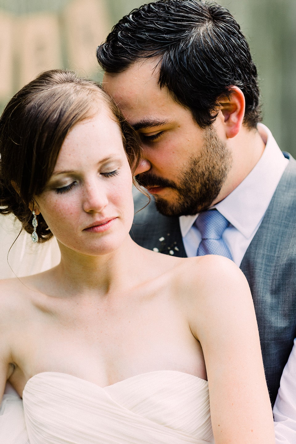 Bride and groom touch foreheads with their eyes closed