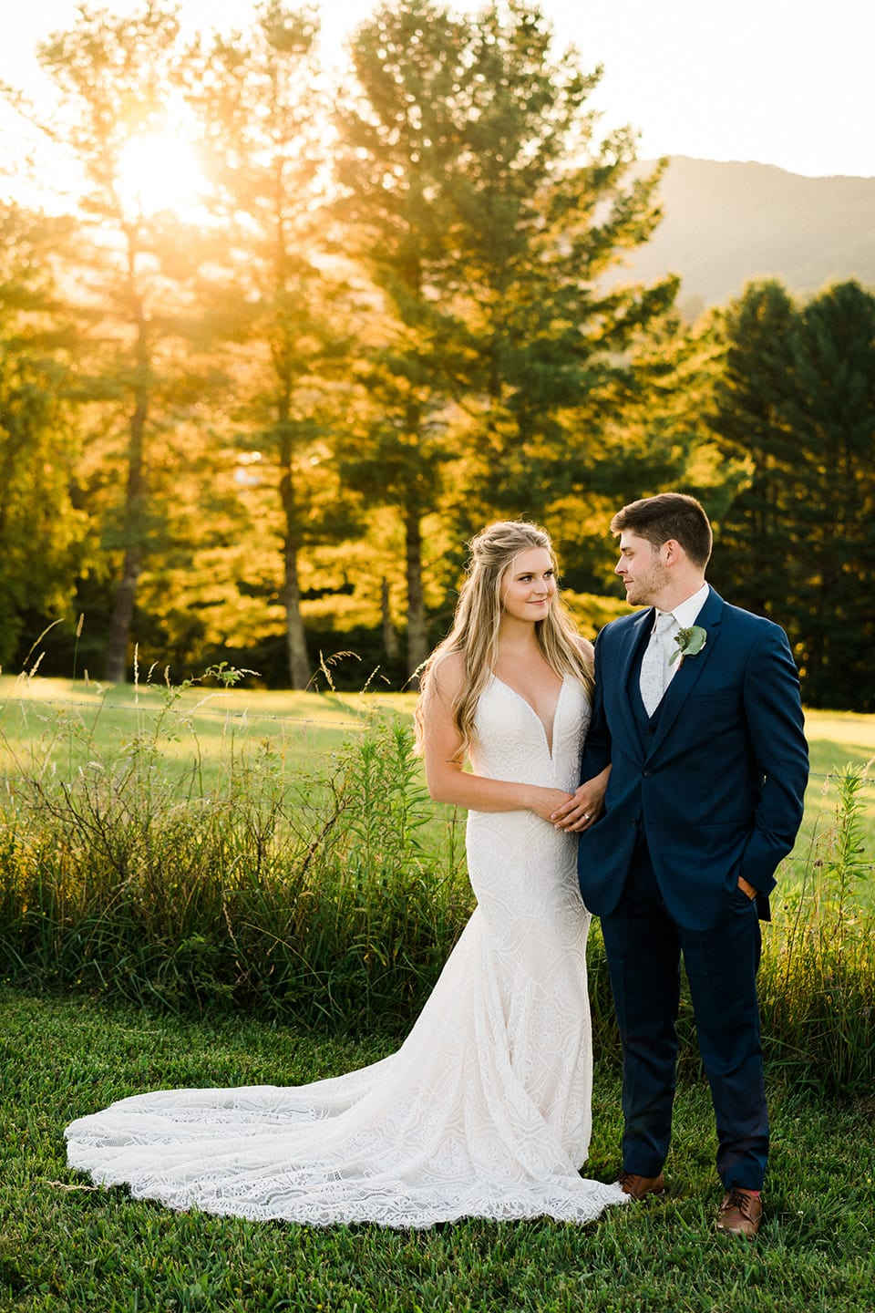 Bride and Groom cuddle in a field at sunset