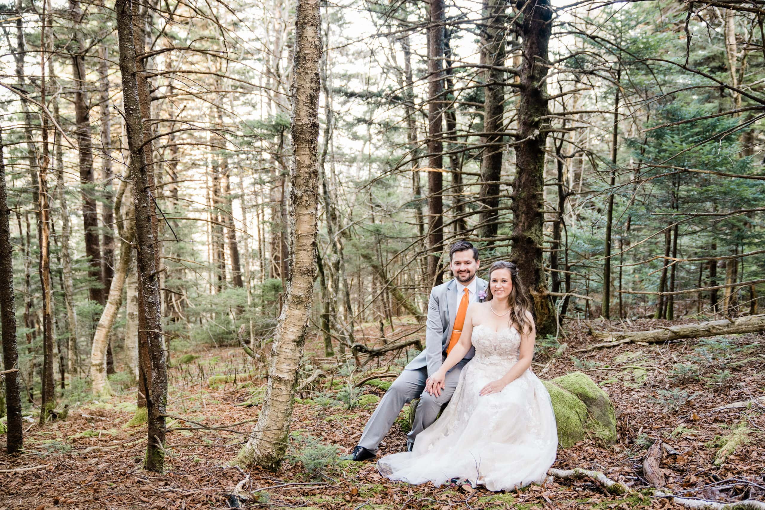 bride and groom sitting on a rock together in the forest