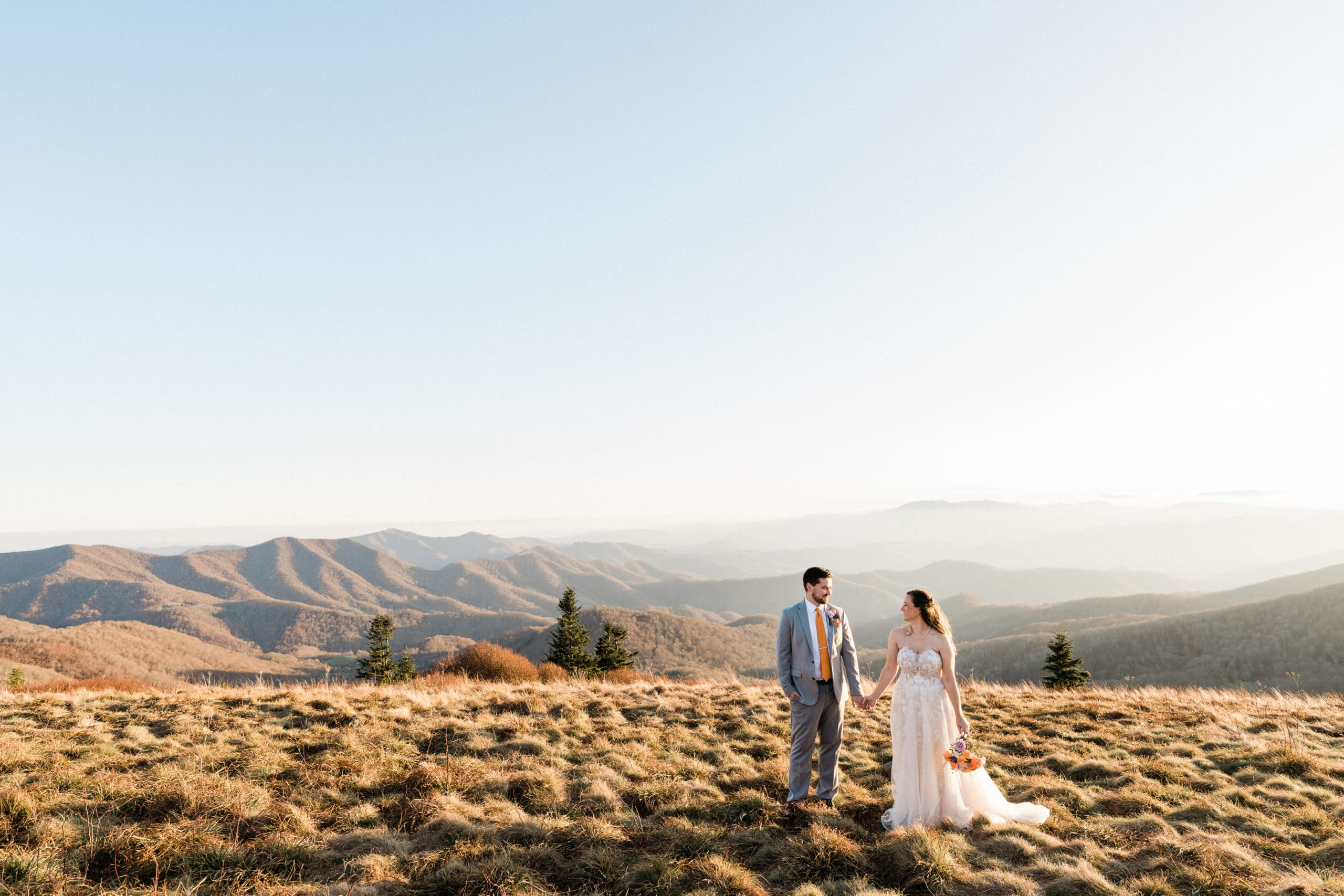 couple holds hands while standing on roan mountain with mountain views in the background