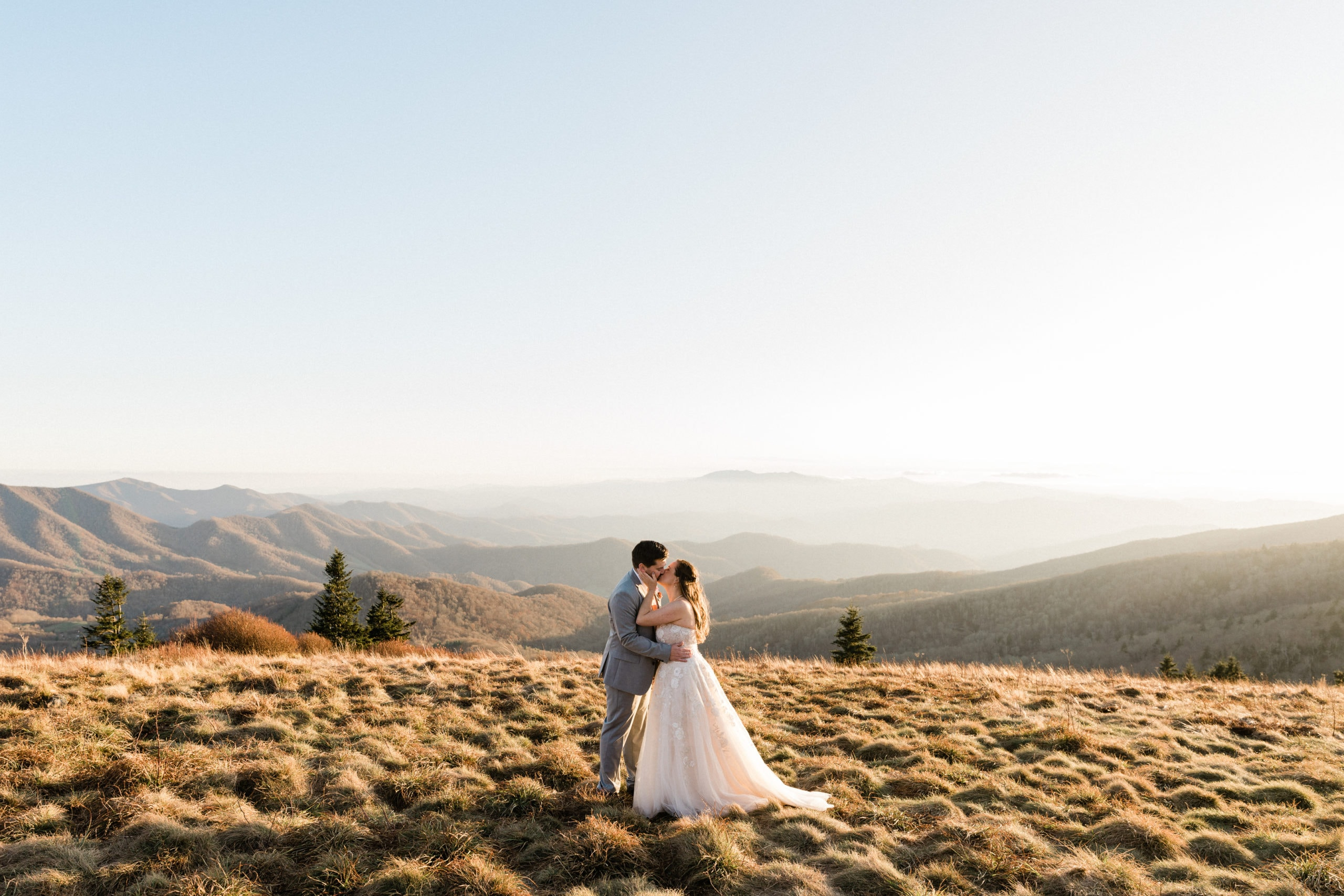 married couple kisses on mountaintop
