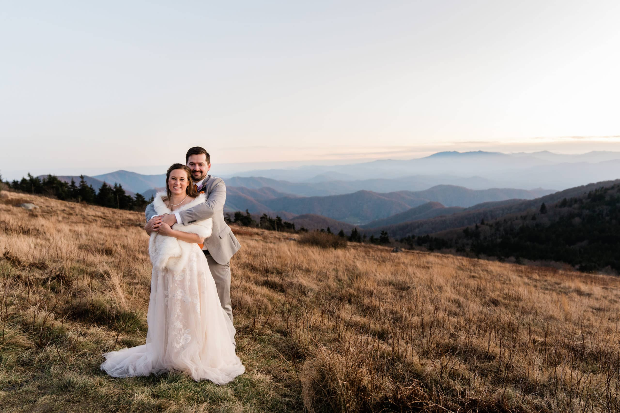 groom hugs bride on top of a mountain