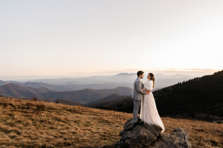 couple embraces on a rock with beautiful mountain views in the background