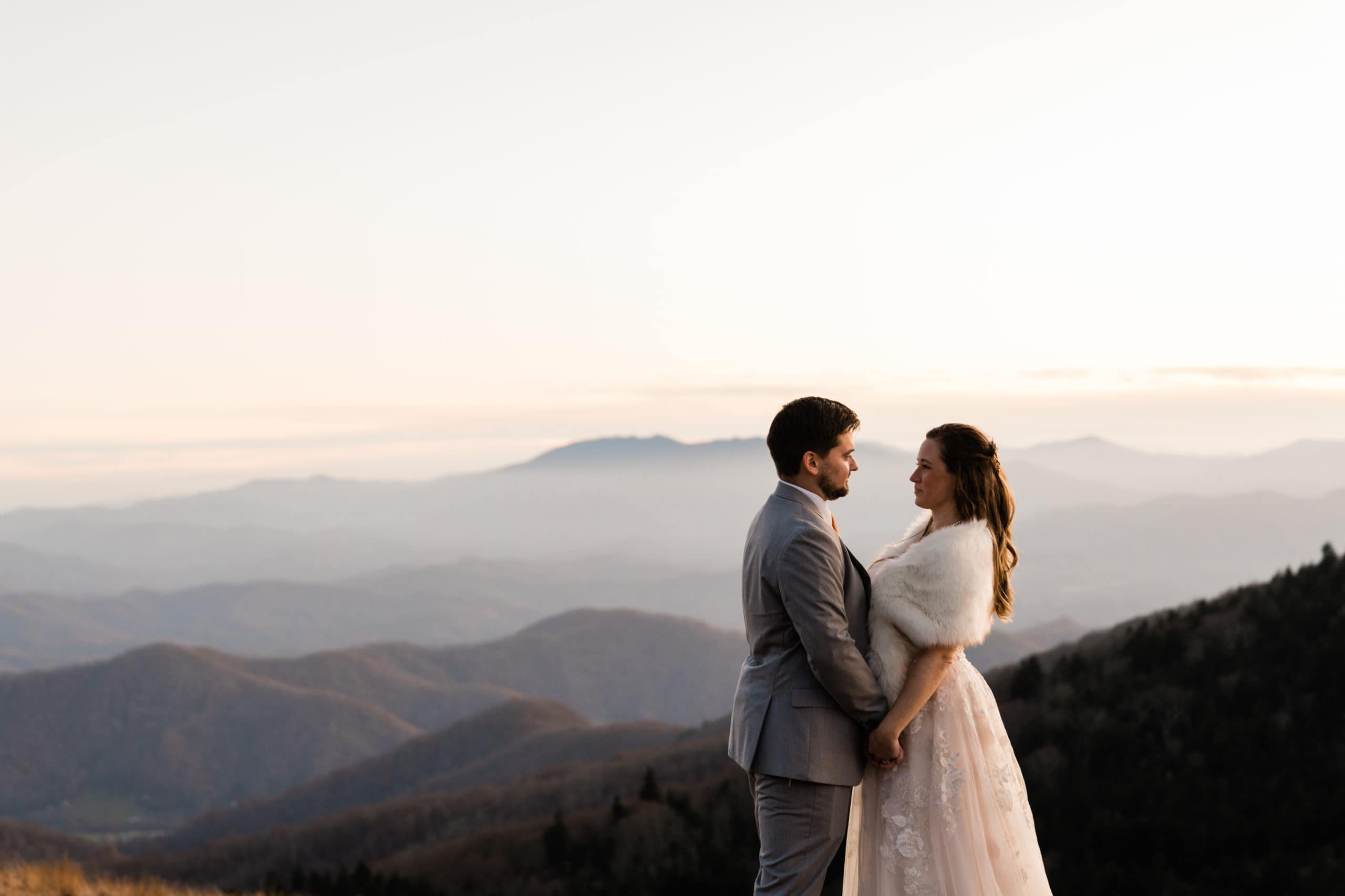 married couple stares into each others eyes with mountains in the background