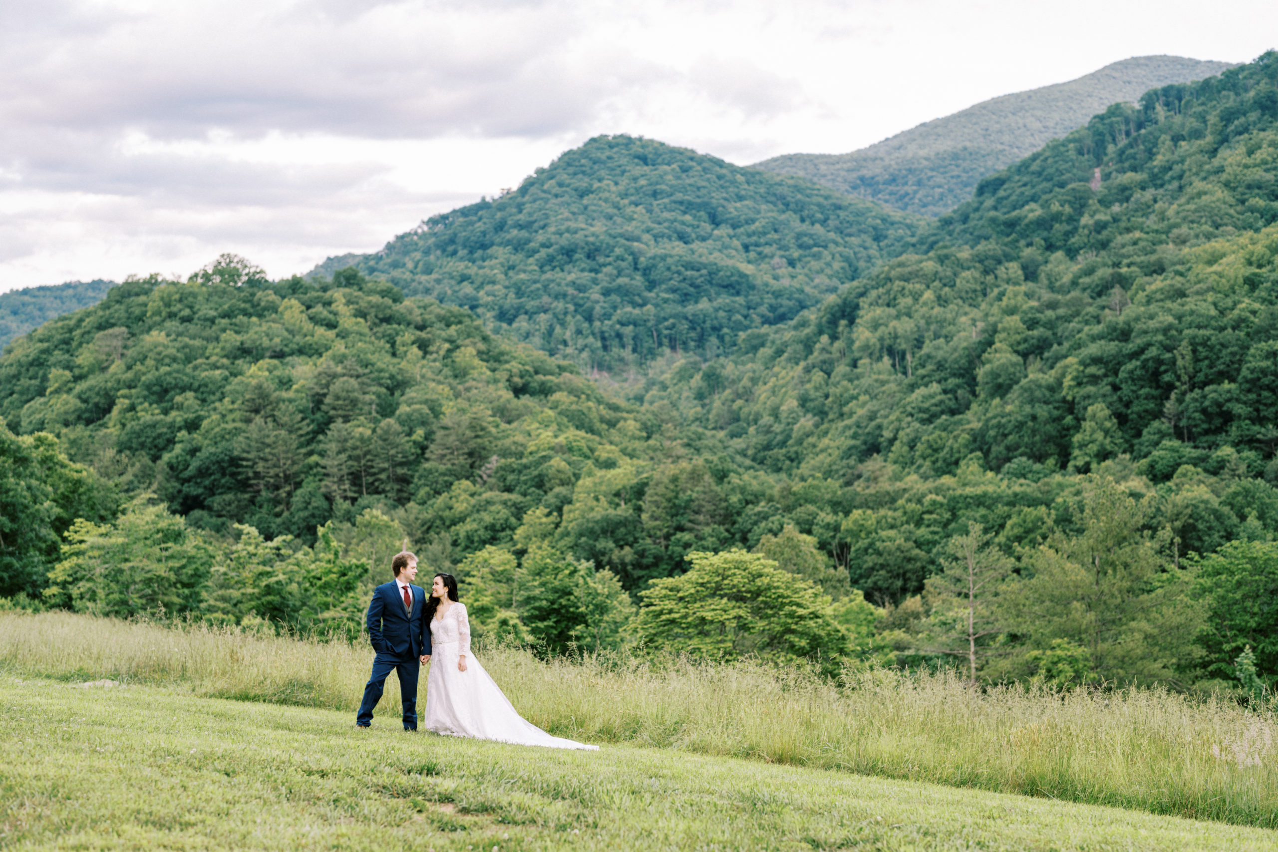 Married couple looks at each other with beautiful mountain views in the background