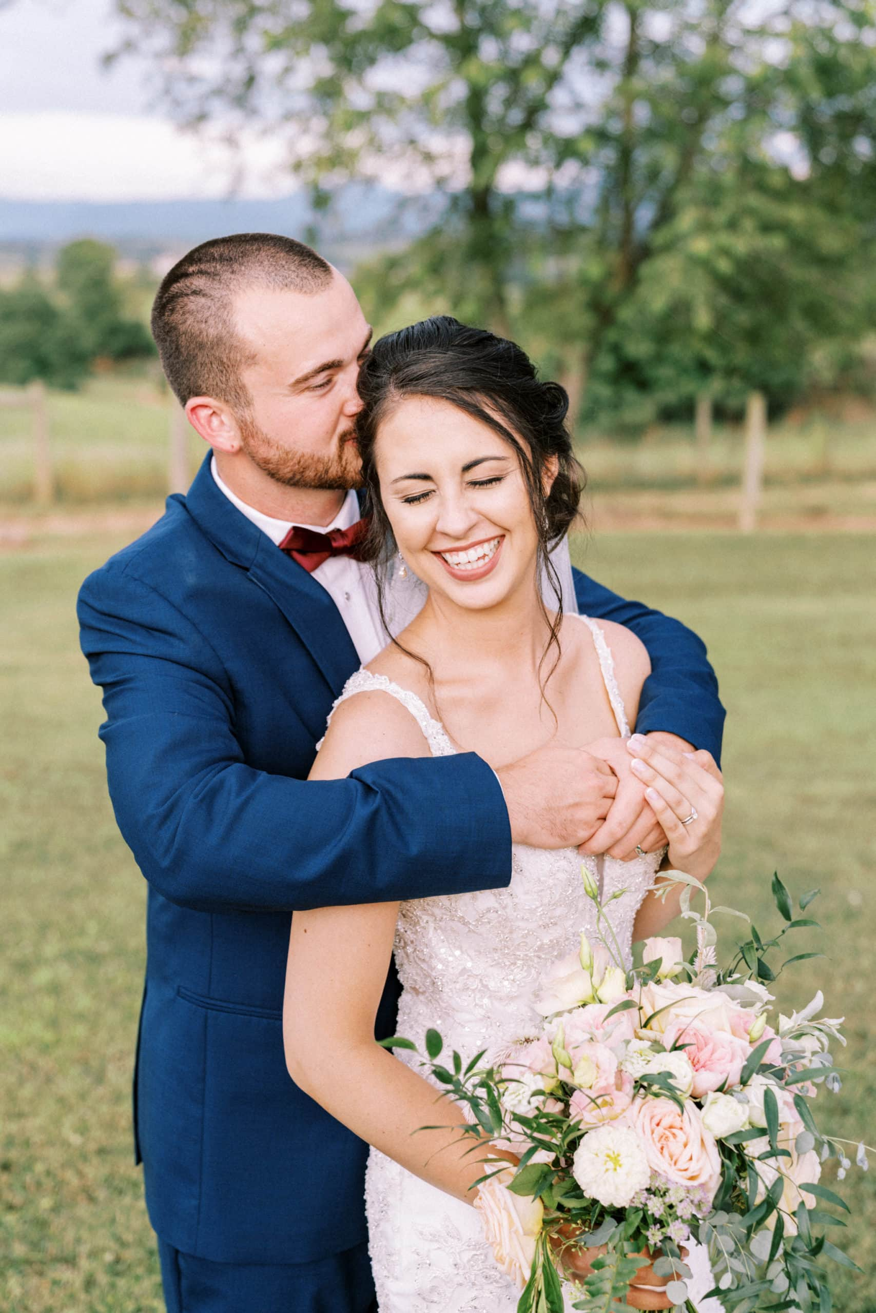 groom hugs wife from behind while smiling