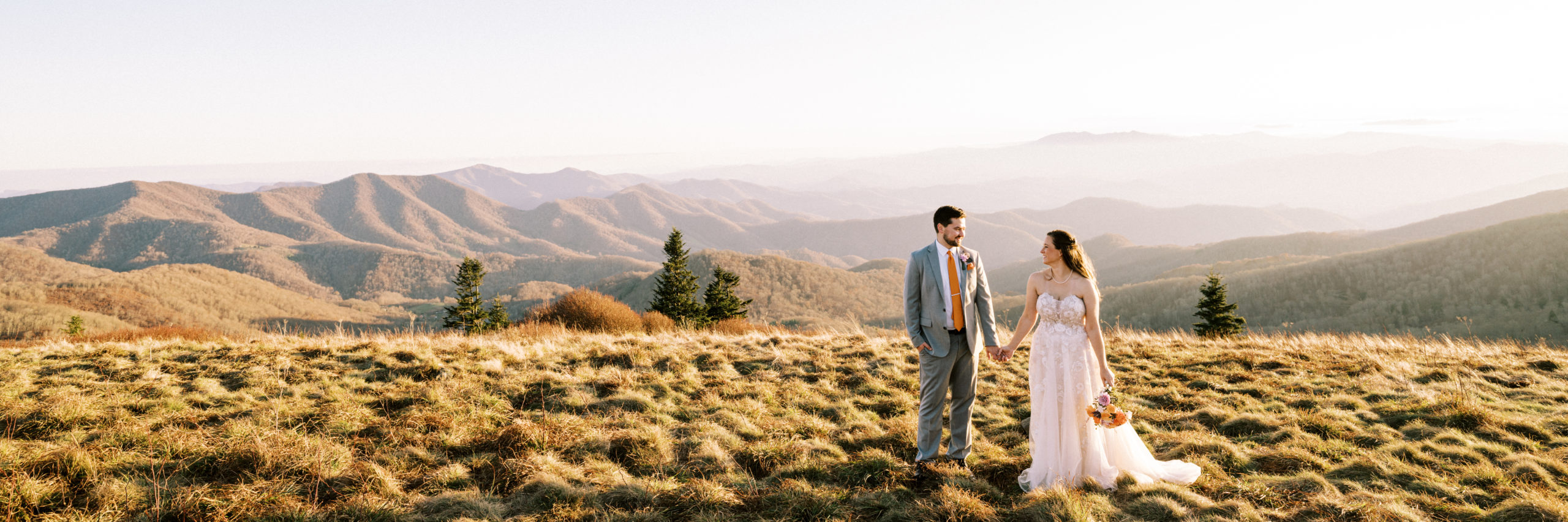 Couple holds hands with beautiful mountain views in the background