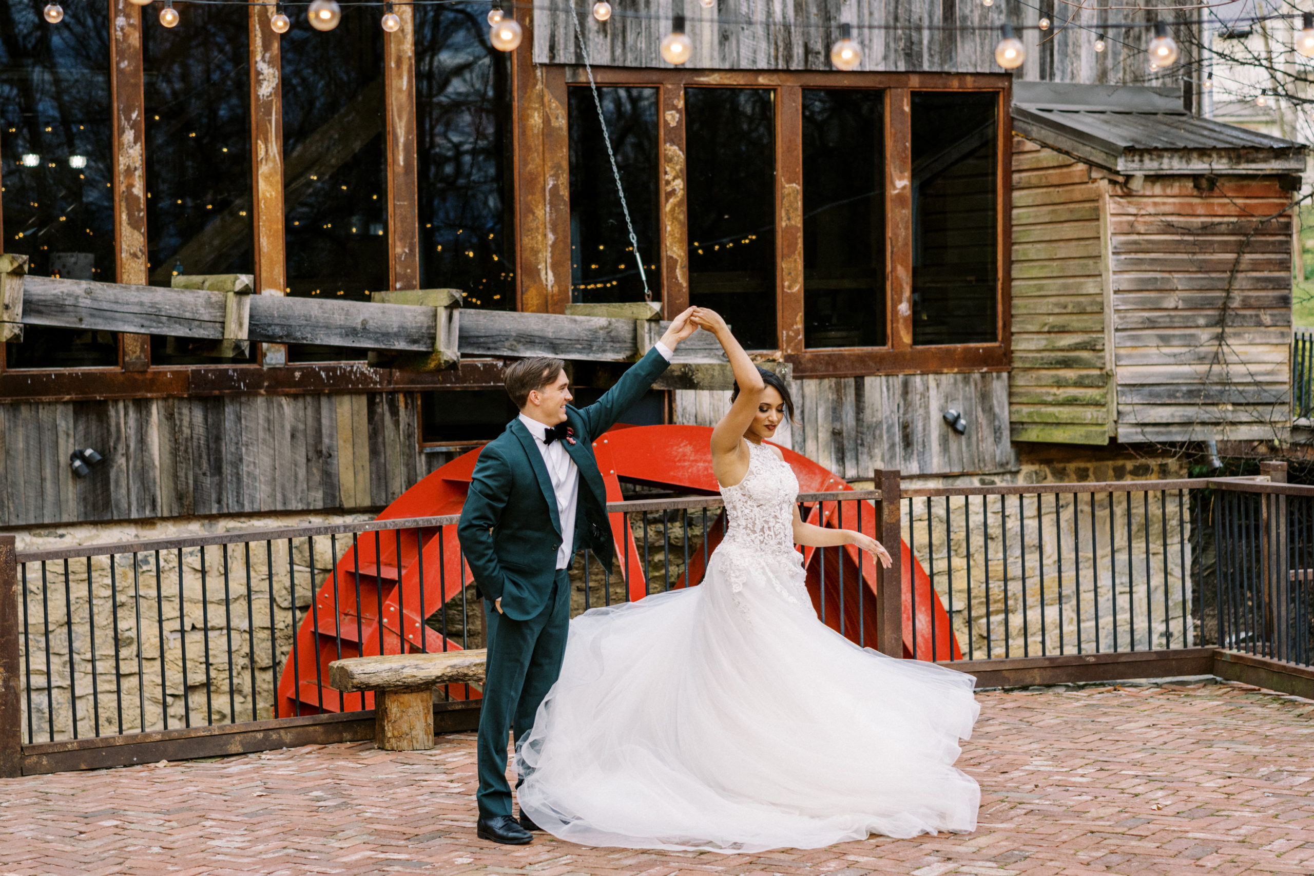 Groom spins his bride while dancing outside in front of a red waterwheel